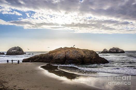 Setting sun against Rocks near San Francisco CA Cliff House by G Matthew Laughton