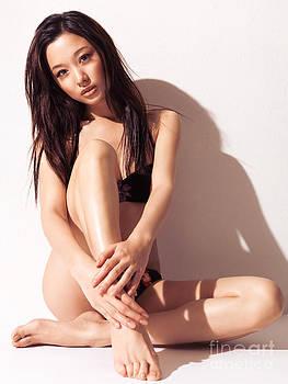 Sexy Japanese woman in bikini sitting against white wall by Oleksiy Maksymenko