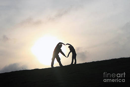 Silhouette Couple forming a heart by Lars Ruecker