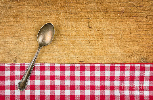 Silver spoon on a wooden board with a checkered tablecloth by Palatia Photo