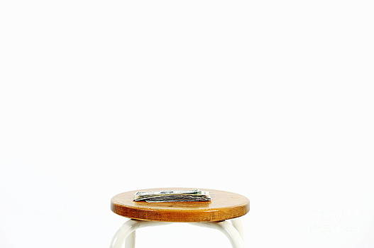 Small amount of US banknotes on stool by Sami Sarkis