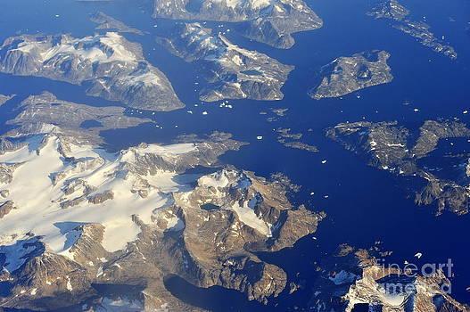 Sami Sarkis - Snowy rocky islands and floating icebergs on ocean