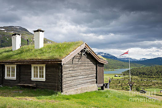 Sod roof log cabin by IPics Photography