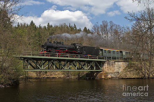 Steam train on a railroad bridge over the pond by Christian Spiller