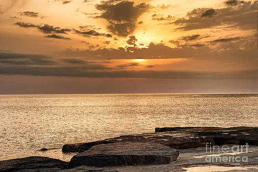 Sun going down over  water glowing on the shore by Alexandr  Malyshev