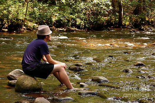 Teen sitting on river rocks by Susan Montgomery