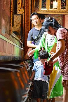 Thai family prying in temple  by Bobby Mandal