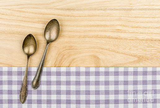 Two silver spoons on a purple checkered table cloth on a wooden background by Palatia Photo