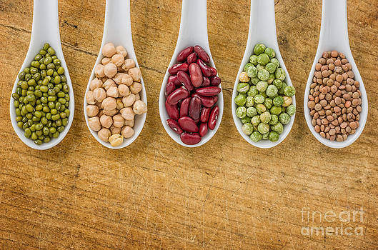 Various legumes on porcelain spoons by Palatia Photo