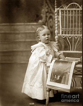 California Views Mr Pat Hathaway Archives - Victorian Little girl standing next to a wicker chair looking at a book circa 1900