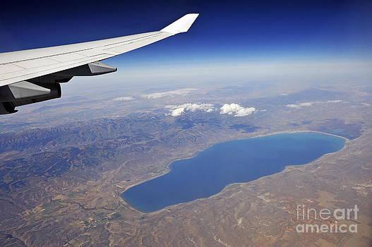 Sami Sarkis - Wing of flying airplane over lake and mountains