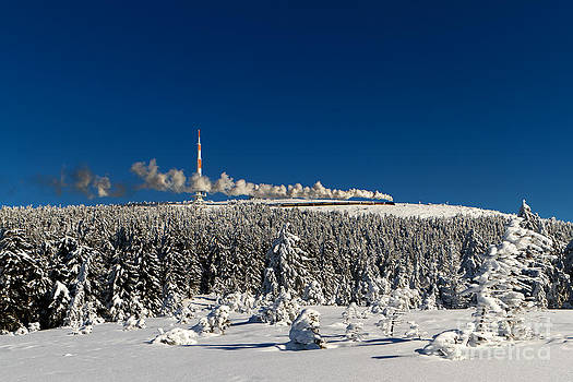 Winterly Brocken mountain with stream train by Christian Spiller