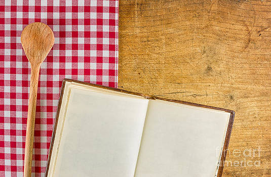 Wooden spoon and book on a wooden board with a checkered tablecloth by Palatia Photo