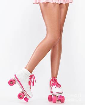 Young woman long legs in pink roller skates by Oleksiy Maksymenko