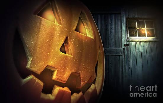 Sandra Cunningham - Glowing pumpkin at night in front of barn door