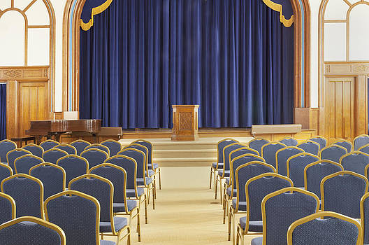 Auditorium With Blue Chairs And A Stage by Douglas Orton