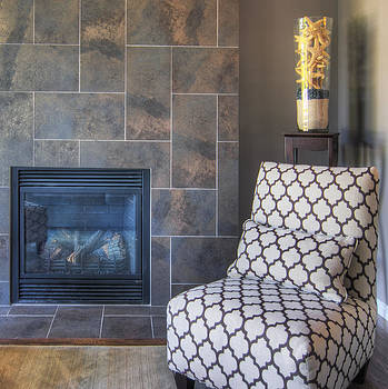 A Tiled Fireplace And A Single Chair by Nicholi Wytovicz