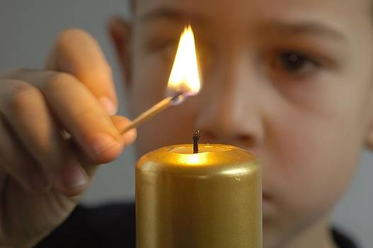 Child lights a candle by Matthias Hauser