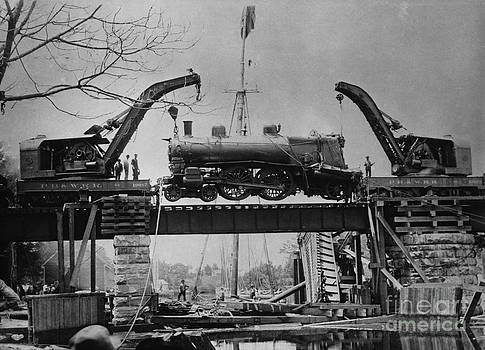 M E Warren and Photo Researchers - Collapsed Bridge and Train Recovery