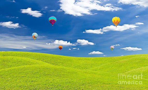 Colorful Hot Air Balloon Against Blue Sky by Mongkol Chakritthakool
