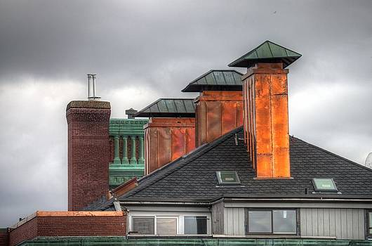 Copper-lined chimneys on a grey sky by Matthew Green
