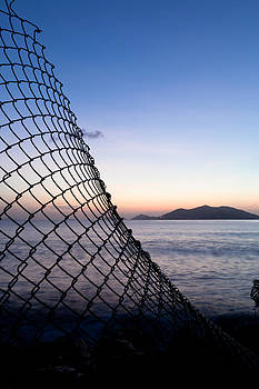 Fence and sunset by the sea in the Caribbean by Anya Brewley schultheiss