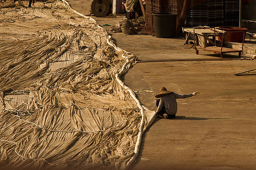 Fisherman sewing net by Gabor Pozsgai