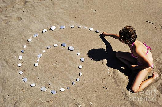 Sami Sarkis - Girl on beach displaying pebbles in spiral shape