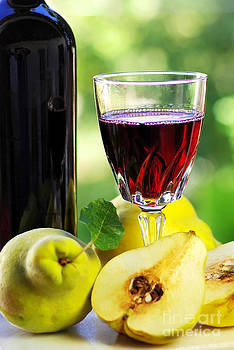 Glass of red wine and quince fruits. by Inacio Pires