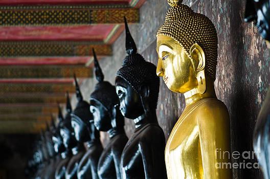 Golden Buddha between black Buddhas by Sattapapan Tratong