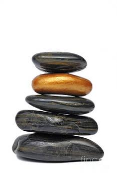 Sami Sarkis - Golden pebble in stack of black pebbles