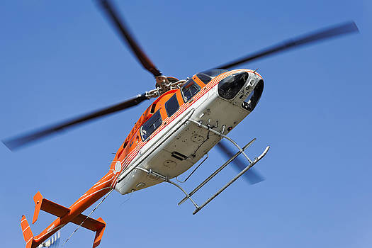 Kantilal Patel - Hovering to land Orange White Helicopter