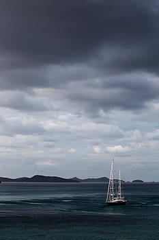 Lone yacht on the sea with dynamic moody clouds by Anya Brewley schultheiss