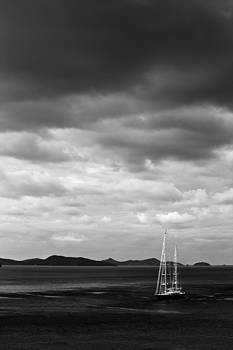 Lone yacht on the sea with dynamic moody clouds in black and white by Anya Brewley schultheiss