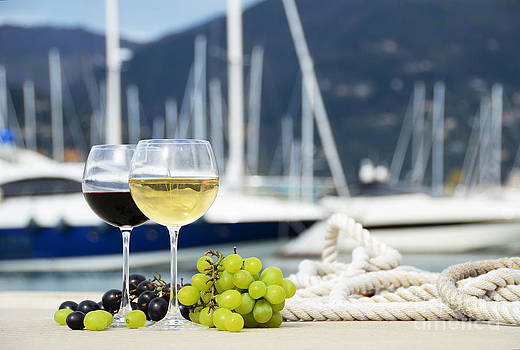 Pair of wineglasses and grapes against the yacht pier of La Spezia by Alexander Chaikin