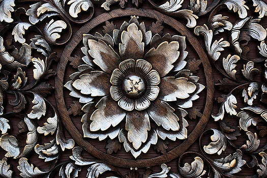 Pattern of flower carved on wood background  by Chaloemphan Prasomphet