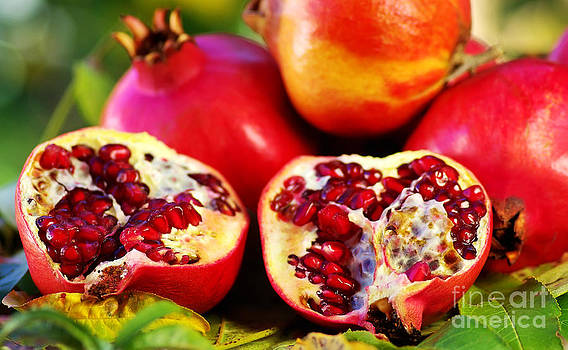 Pomegranates  on table. by Inacio Pires