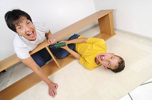 Screaming mother and son assembling furniture by Matthias Hauser