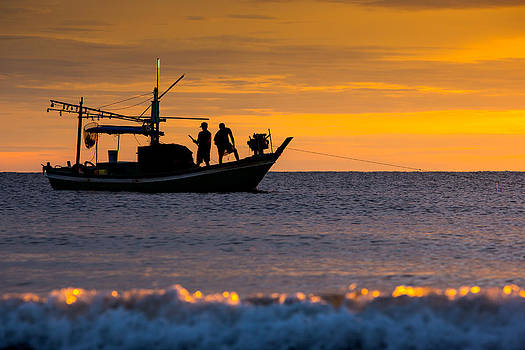 Silhouette fisherman on boat in sunset huahin by Arthit Somsakul
