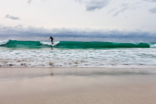 Single surfer on the waves on an overcast day by Anya Brewley schultheiss