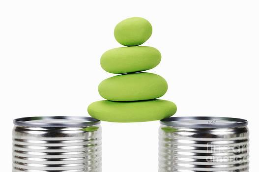 Sami Sarkis - Stack of green pebbles balancing between tin cans