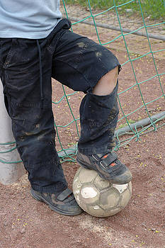 Street soccer - torn trousers and ball by Matthias Hauser