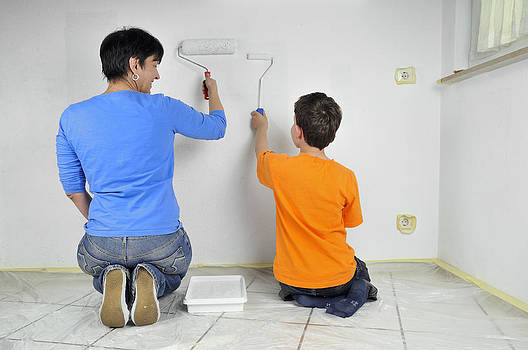 Teamwork - Mother and child painting wall by Matthias Hauser