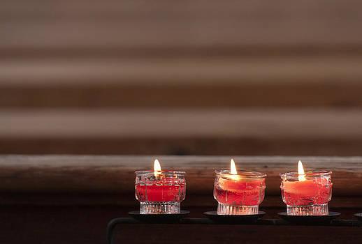 Three candles burning in a church by Matthias Hauser