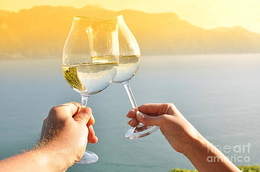 Two hands holding wineglases by Alexander Chaikin