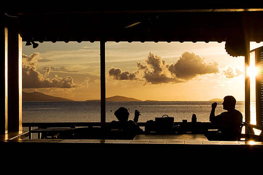 Two people watching the sunset at Cane garden bay Virgin Islands by Anya Brewley schultheiss