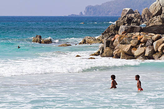 Vibrant blue Caribbean seascape with two children walking into the water. by Anya Brewley schultheiss