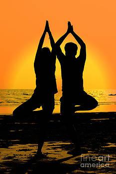 Yoga pose. Sunset silhouette. by Pongsak Deethongngam