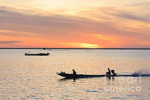 Fisherman in fishing boat by Buchachon Petthanya