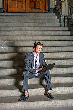 Alexander Image - American Businessman working on laptop, sitting on stairs